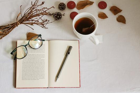 オフィスのデスク。ノートパソコン、書類ケース、スマホ、手帳、マグカップが置かれている。椅子の背面に観葉植物。