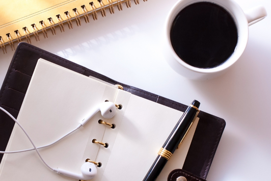 広げられたシステム手帳のうえに置かれたイヤフォンと万年筆。リングノート。ブラックコーヒーの入ったマグカップ。