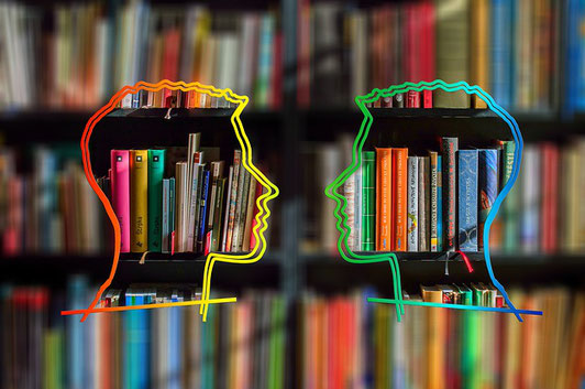 本棚の前で男性社員2人がひそひそ話。