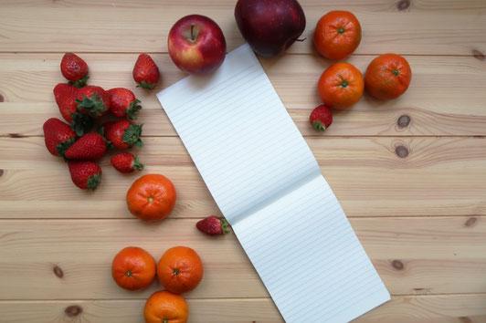 広げられた白紙のリング式ノート。ピンクの花とリボンのコサージュ。白の万年筆。