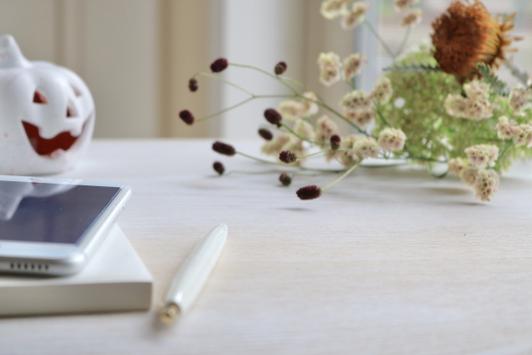 積まれた手帳の上に置かれた電卓。水色と花柄の手帳。スマートフォン。