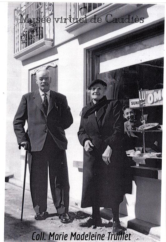Laurent Laffite (père de Fernande épouse Truillet) et   Léonie Truillet (née Jeantet,  épouse de Jean, mère d'Augustin Truillet) devant l'épicerie.