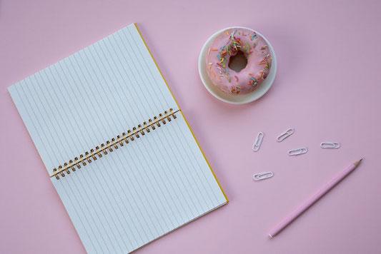 デスクに広げられたビジネスグッズ。タブレット、メモ帳、ゼムクリップ、鉛筆、付箋。飲みかけのコーヒーが入ったマグカップ。