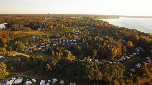 Die Blockhäuser stehen am Rande des Campingplatzes mit Blick auf eine große Wiese und zwischen zwei Seen. © Naturcamping Zwei Seen am Plauer See/MV