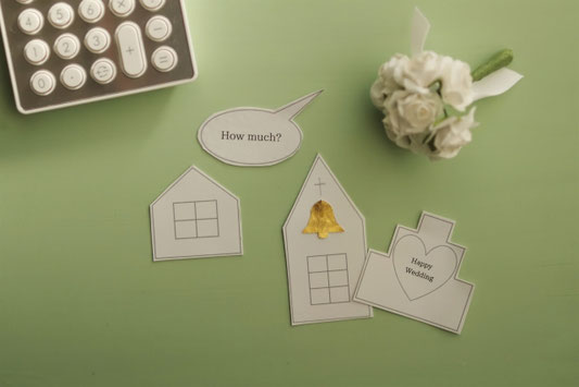 電卓とミニチュアサイズのウェディングブーケ。家、教会、ウェディングケースのかたちをしたペーパークラフト。結婚するといくらかかるの?