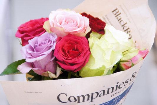 ノートパソコンのキーボードの上に置かれた電卓と虫眼鏡。メモ帳とボールペン。観葉植物。