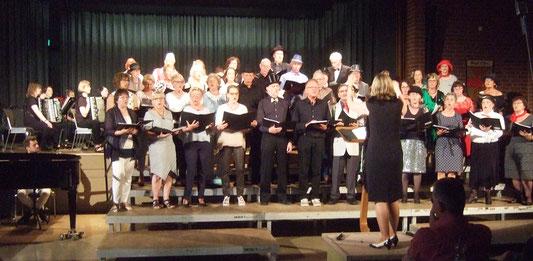 Die Chormitglieder stehen auf der Bühne, Sigrid Hartmann gibt den Takt an und Datastico sitzt schon im Hintergrund.