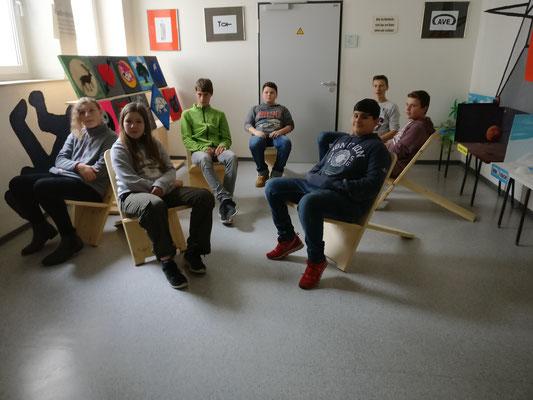 """Die Schülerinnen und Schüler des Angebots """"Arbeiten mit Holz"""" auf ihren Stühlen"""