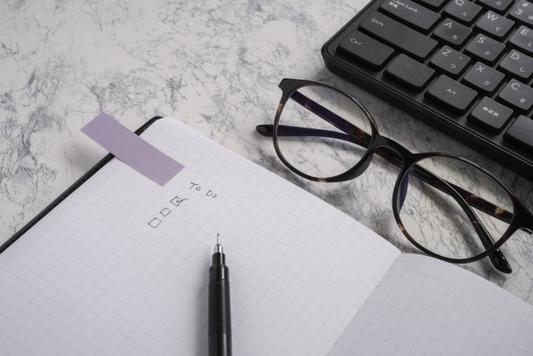 パソコンのキーボード。ピンクの手帳の上に置かれたピンクの目覚まし時計。ゴールドのボールペンとメモパッド。