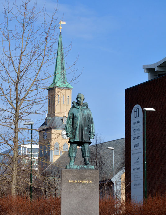 Bronze statue of Roald Amundsen (1872-1928) and the Domkirke, Tromso. He died in a plane crash on a rescue mission somewhere north of Tromso in the Barents Sea. His body was never recovered.