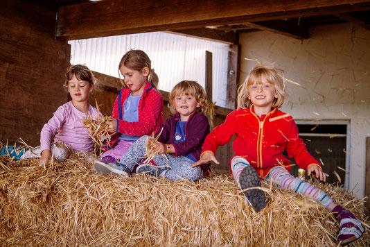 Kinder spielen auf einem Heuballen im Stall