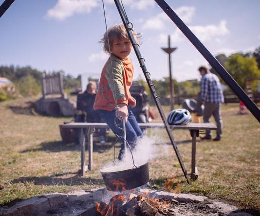 Kochen von Stockbrot und Kartoffelsuppe über einem knisternden Lagerfeuer