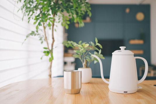 カフェの店内。テーブルに置かれたケトルとカップ。観葉植物の鉢植え。