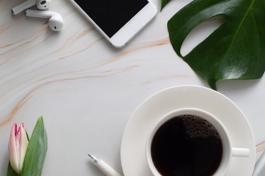 コーヒーの入ったカップ&ソーサ。スマートフォンとイヤフォン。ボールペン。モンステラの葉。ピンクのチューリップ。