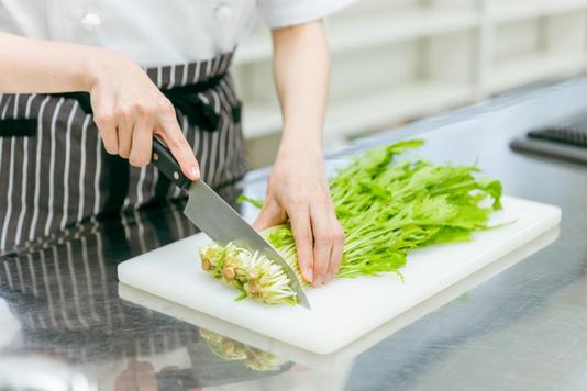 深緑のエプロンに白シャツ姿のカフェの店員が3人並んで立っている。