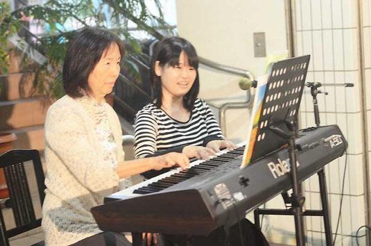 軽やかな電子ピアノの音色を響かせる宮地さん(右)と生徒=ライブスポットななサン丸