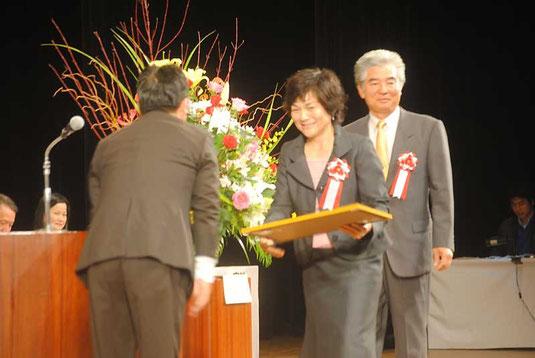 北川会長から表彰される八重山地区の山里世紀子さん、野底一彦さん=30日午後、市民会館大ホール