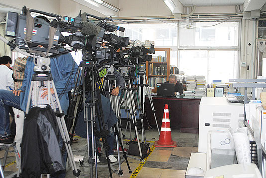 Jアラートの前に陣取る報道陣=10日正午ごろ、市役所
