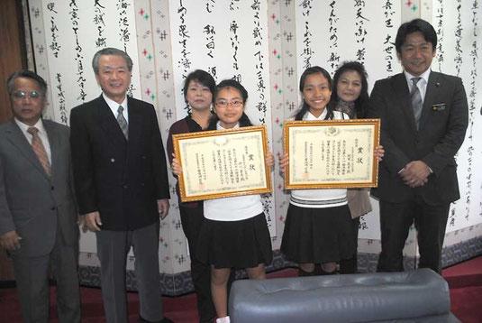 砂川さん(中央左)、迎里さん(同右)の家族と学校関係者が中山市長に受賞を報告した=29日午後、市役所
