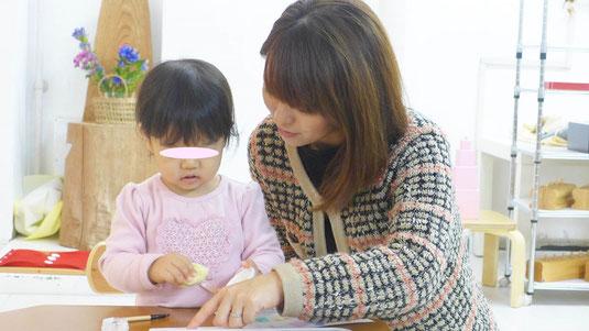 モンテッソーリ活動で、ステッラコースのお子様をお母様がサポートしています。