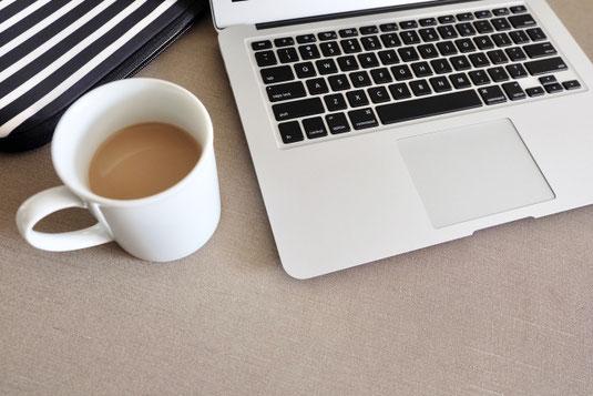 ページが開かれた本のうえに置かれた眼鏡。トレイに載ったチョコチップクッキーとハーブティー。ガラスの器に活けられたカモミールの花。