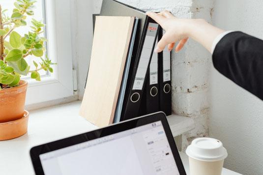 陽ざしが差し込むデスクでノートパソコンに打ち込む指先。