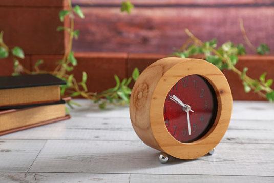 木製の置時計。積まれたハードカバーの本。観葉植物のつる。