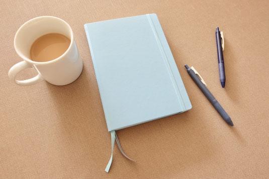 デスクに置かれた置時計。コーヒーの入ったマグカップ。ページが開かれた白紙のノートと万年筆。淡いピンクの小花が一輪。