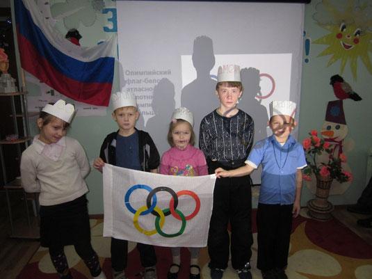 Учащиеся младших классов с олимпийским флагом