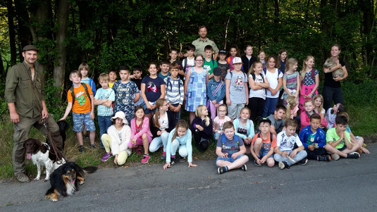 Foto: Klasse 3 a/b der GGS Alzenbach-Mühleip, Jagdaufseher Christopher Kirschbaum, Eheleute Wild mit Frischlingen und Jagdhunden