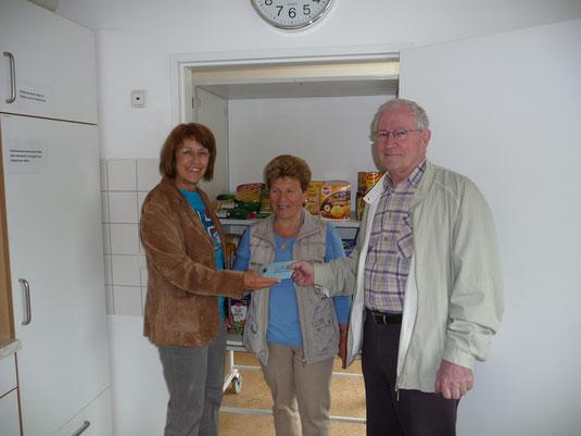 Das Bild zeigt Petra Ensberg und Gerhard Langenbach vom Tauschring bei der Spendenübergabe an eine Helferin der Essensbank.