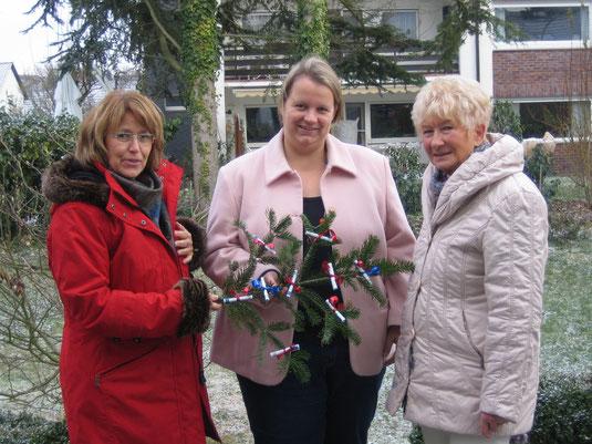 Das Foto zeigt die Pfarrerin Dr. Erichsen-Wendt von der evangelischen Kirche bei der Geldübergabe - passend zur Weihnachtszeit mit Tannenzweig - durch Petra Ensberg und Barbara Geisler vom Nidderauer Tauschring.