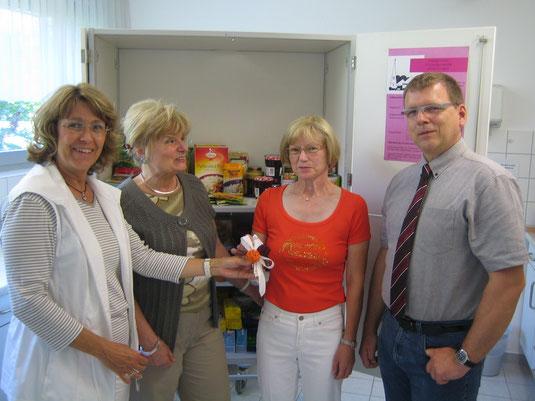 Auf dem Foto sehen Sie Iris Müller (2. von li.) und Petra Ensberg vor dem Lebensmittelschrank  der Essensbank bei der Geldübergabe an Frau Höhl und Herrn Pfarrer Beuthert.