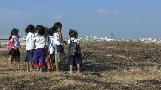 Ces enfants scolarisés qui regardent au loin la ville de Phnom Penh ont sous leurs pieds l'ancienne décharge aujourd'hui fermée.