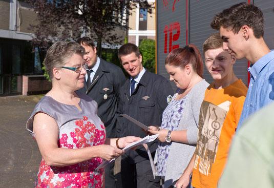 JPRS-Schulleiterin Jutta Tschakert überreicht den Schülern die Würdigungsurkunde in Form eines Zeugnisbeiblattes.
