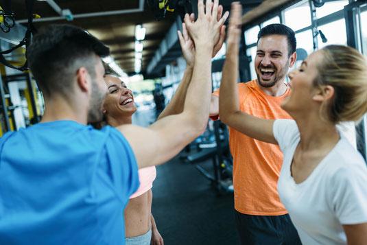Fitnessgruppenteilnehmer geben sich high Five nach erfolgreich bestandenen Personal Trainer Übung durch Anuschka Schielin in Düsseldorf