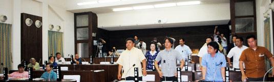 国に尖閣諸島の購入を求める意見書の表決で、起立して賛成する与党(右側)と着席したままの野党=19日午前、市議会