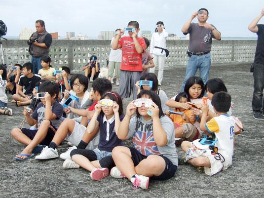 部分日食を観察する児童たち=21日午前、石垣小学校