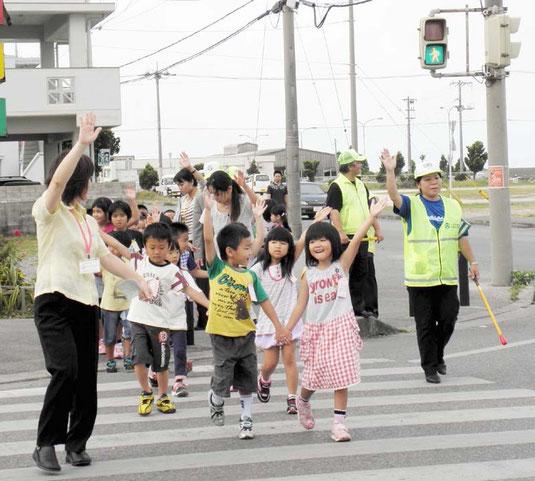 左右を確認し、手を挙げて横断歩道を渡る新入学児童=八島小付近交差点
