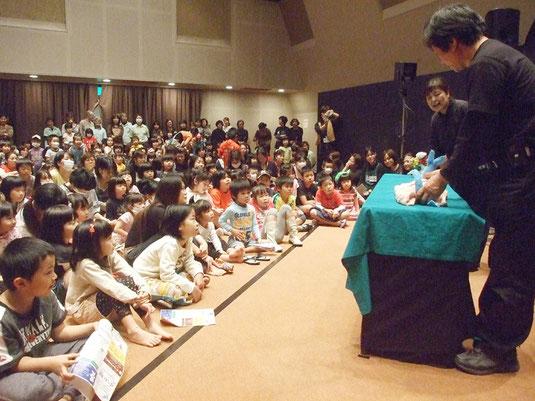 人形劇に見入る子どもたち=12日午後、市民会館中ホール