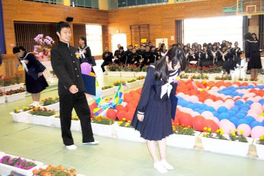 式を終え、来賓席に頭を下げる卒業生=10日午前、白保中体育館