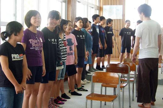 劇団四季の俳優から指導を受ける児童たち=6日午前、石垣小学校