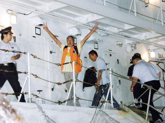 「また、尖閣に来る」と主張し、Vサインで乗り込む抗議船乗組員ら=17日午後8時過ぎ、石垣港
