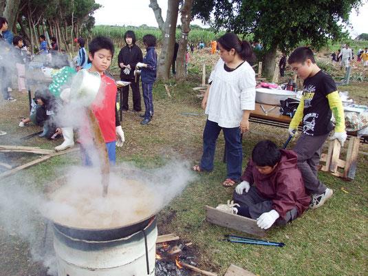 黒糖づくりに取り組む5年生児童たち=12日午前、宮良小学校