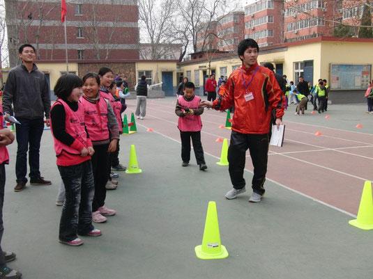 北京で開かれた国際陸連の講座の課題で北京語を使い、子供たちを指導する泉水さん(右)=提供写真、北京、3月22日