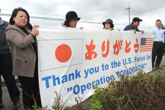 米軍機に向け、トモダチ作戦への感謝の横断幕を掲げる八重山防衛協会関係者ら(13日午後)