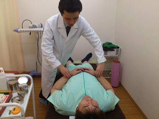 東洋医学の診断法、『切診』を行っているところ