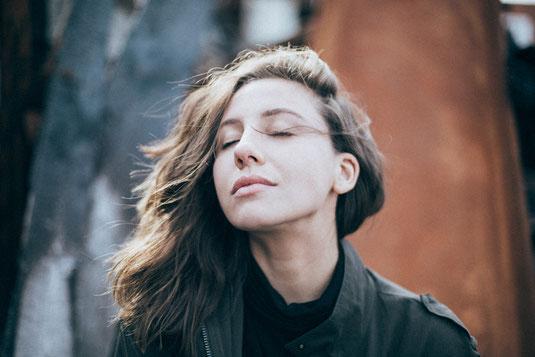Eine junge Frau atmet tief ein