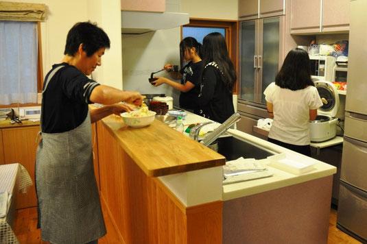 食事の準備をするお母さんと手伝う生徒たち
