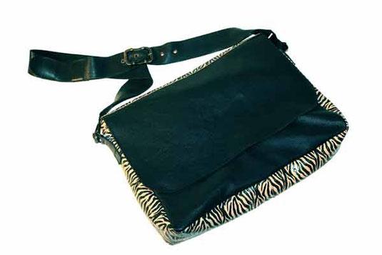 Cette photo représente le sac Ernestine, nouvelle création de maroquinerie aux Sabots d'Isa, une grande besace en cuir noir et cuir zébré, avec des mousquetons noirs et une grosse boucle de ceinture en laiton vieilli.